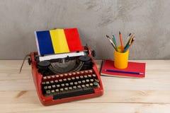 Polityczny, wiadomość i edukacja pojęcie, - czerwona rocznik maszyna do pisania, flaga Rumunia, ołówek zdjęcie royalty free