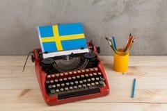 Polityczny, wiadomość i edukacja pojęcie, - czerwona rocznik maszyna do pisania, flaga Szwecja, ołówek zdjęcie royalty free
