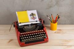 Polityczny, wiadomość i edukacja pojęcie, - czerwona rocznik maszyna do pisania, flaga watykan, ołówek fotografia stock