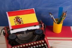 Polityczny, wiadomość i edukacja pojęcie, flaga Hiszpania, książka i materiały na stole - czerwona maszyna do pisania, fotografia royalty free