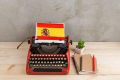Polityczny, wiadomo?? i edukacja poj?cie, flaga Hiszpania i notatniki - czerwona maszyna do pisania, zdjęcie royalty free