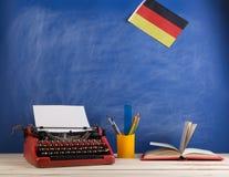Polityczny, wiadomość i edukacja pojęcie, flaga Niemcy, książka i materiały na stole - czerwona maszyna do pisania, zdjęcia royalty free