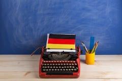 Polityczny, wiadomość i edukacja pojęcie, flaga Niemcy i materiały na stole - czerwona maszyna do pisania, zdjęcie stock