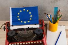 Polityczny, wiadomość i edukacja pojęcie, flaga unia europejska, notatnik i materiały - czerwona maszyna do pisania, obrazy stock