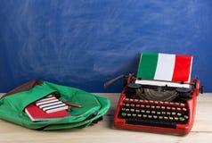 Polityczny, wiadomość i edukacja pojęcie, flaga Włochy, zielony plecak i materiały na stole - czerwona maszyna do pisania, zdjęcie stock