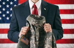 Polityk: Trzymać wojskowy uniform kurtkę obrazy royalty free