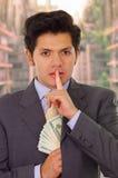 Polityk w ciemnym kostiumu z krawata kładzenia pieniądze w jego kostiumu i obraz stock