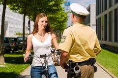 Polizei - Frau auf Fahrrad mit Polizeibeamten Stockfotos