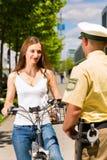 Polizei - Frau auf Fahrrad mit Polizeibeamten Stockfoto
