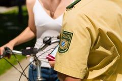 Polizei - Frau auf Fahrrad mit Polizeibeamten Stockfotografie