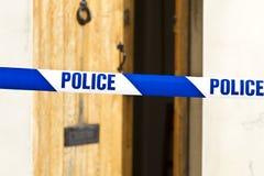 Polizei nimmt über einer offenen Tür auf Band auf Stockfotografie