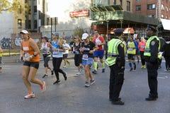 Polizei schaut, während Läufer in Manhattan an NYC-Marathon teilnehmen stockfoto