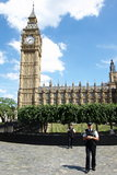 Polizei steht Abdeckung außerhalb des Palastes von Westminster Stockbilder