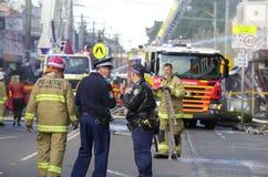 Polizei und Feuerwehrmänner nehmen an Explosionsexplosion am Shop teil Stockbild