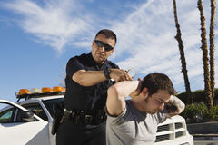 Polizeibeamte Arresting Young Man Lizenzfreie Stockbilder