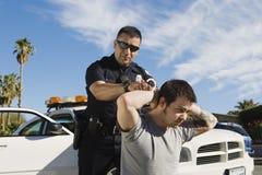 Polizeibeamte Arresting Young Man Stockbild