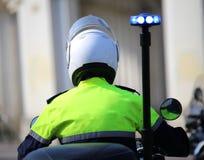 Polizeibeamte auf Motorrad mit blinkender blauer Sirene in der Stadt Lizenzfreie Stockfotografie
