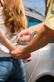 Polizeibeamte, der eine Frau mit den Handschellen festnimmt Lizenzfreie Stockfotos