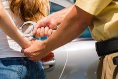 Polizeibeamte, der eine Frau mit den Handschellen festnimmt Lizenzfreies Stockbild