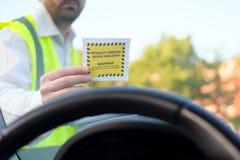 Polizeibeamte, der eine Geldstrafe für parkende Verletzung gibt Lizenzfreie Stockbilder