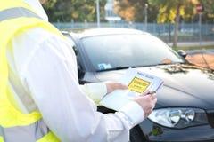 Polizeibeamte, der eine Geldstrafe für parkende Verletzung gibt Lizenzfreie Stockfotografie
