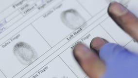 Polizeibeamte, der Fingerabdrücke des Hauptverdächtigen, biometrisches Kennzeichen des identifizierenden Merkmals nimmt stock video footage