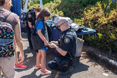 Polizeibeamte, der Kevlar-Weste auf ein Kind setzt lizenzfreie stockbilder