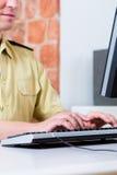 Polizeibeamte, der an Schreibtisch in der Abteilung arbeitet Stockfoto