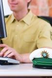 Polizeibeamte, der an Schreibtisch in der Station arbeitet Lizenzfreie Stockfotos