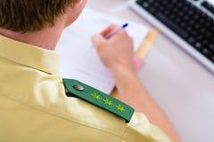 Polizeibeamte, der an Schreibtisch in der Station arbeitet Lizenzfreies Stockfoto