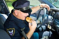 Polizeibeamte, die Krapfen isst Stockbild