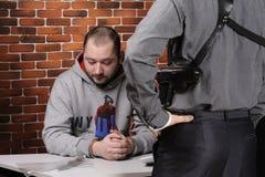 Polizeibeamte fragt Häftling ab Stockfotos