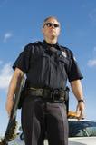 Polizeibeamte Holding Weapon Stockfoto