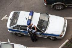 Polizeibeamte macht einen Eintritt, der auf dem Autodach sich lehnt Stockfotografie