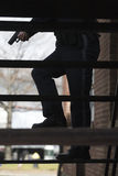 Polizeibeamte mit dem gezogenem Pistolesuchen. Stockfotografie