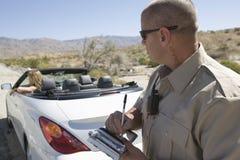Polizeibeamte Writing Traffic Ticket zur Frau im Auto Lizenzfreie Stockfotos