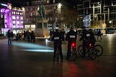 Polizeibeamten auf dem Fahrrad, das Leute und Kerzen betrachtet Lizenzfreie Stockfotos