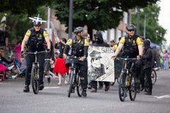 Polizeibeamten auf den Fahrrädern, die entlang Seitenantispindel reiten, maskierten Demonstranten stockfotos
