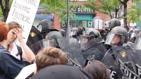 Polizeibeamten in der Linie Blockdemonstranten an der beschäftigten Ecke stock video