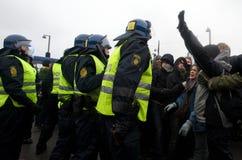 Polizeibeamten, die gegen eine Masse umziehen Lizenzfreie Stockfotos