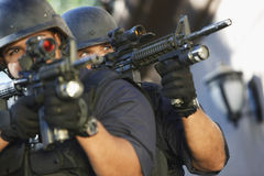 Polizeibeamten, die mit Gewehren zielen Stockbilder