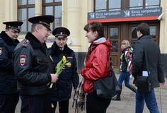 Polizeibeamten geben Blumen zum women& x27; s-Tag Lizenzfreies Stockfoto