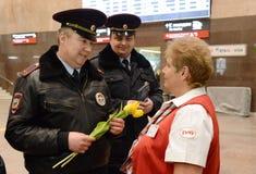 Polizeibeamten geben Blumen zum women& x27; s-Tag Lizenzfreie Stockfotos