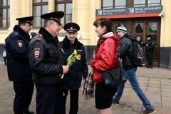 Polizeibeamten geben Blumen zum women& x27; s-Tag Stockfoto