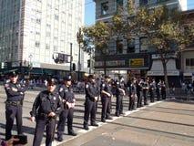 Polizeibeamten stehen in der Zeile über Marktstraße Stockbild