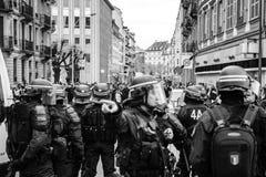 Polizeibeamten, welche die Zone vor gelben Jacken Gil sichern stockbilder