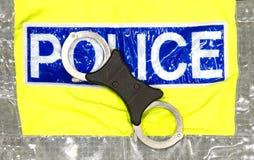 Polizeihandschellen auf einer hallo visibilty Jacke Stockbild