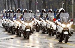 Polizeimotorradfahrer in der Anordnung Lizenzfreie Stockfotos