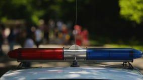 Polizeisirenenbeleuchtung auf Patrouillenfahrzeug, dringende Evakuierung von Leuten, Notfall stock footage