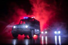 Polizeiwagen, der ein Auto nachts mit Nebelhintergrund jagt Polizeiwagen mit 911 Notfallschutzen, der zur Szene des Verbrechens b stockbild